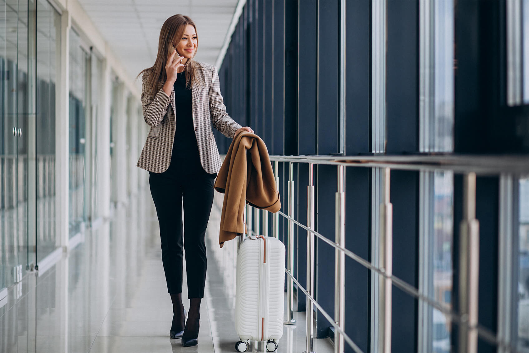 business-woman-terminal-with-travel-bag-talking-phone